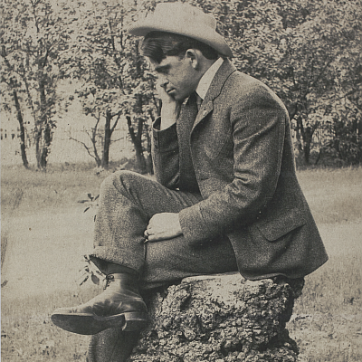 Jack London sitting on a stump, photographed between 1910 and 1915